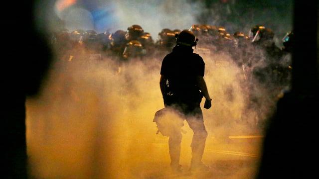 Numerus policists stattan en in nivel da gas lacrimogen.