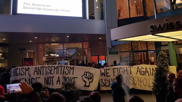 """Menschenmenge vor einem Gebäude, einige halten Plakate. Aufschrift: """"Racism, Antisemitism... not a joke."""""""