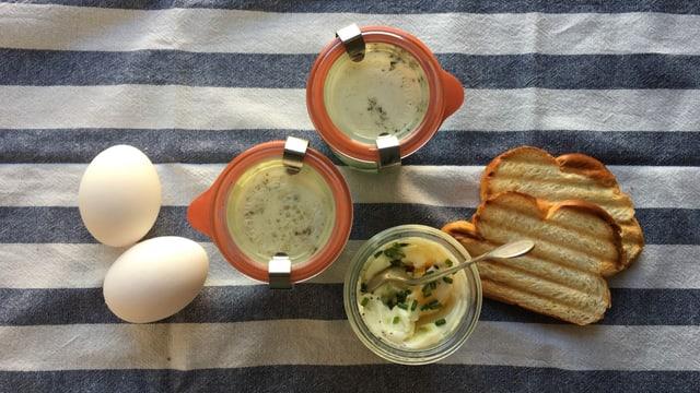 Drei Weckgläser mit Oeufs en cocotte und getoastetes Brot.