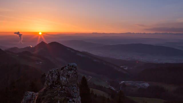 Orange Sonne am Horizont. Die Hügel liegen noch im Schatten.