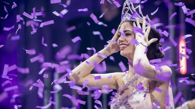 Die neue Miss Schweiz strahlt nach ihrem Sieg auf der Bühne während Konfetti über ihr Haupt rieseln.