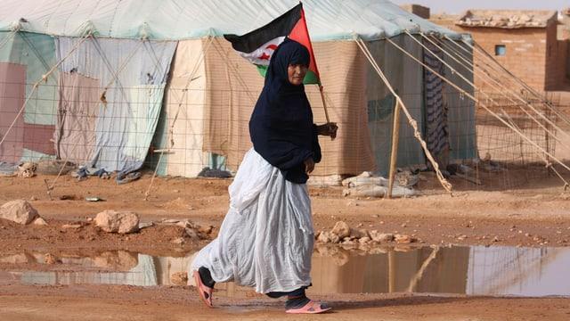 Eine Frau in einem Flüchtlingscamp an der algerischen Grenze hält eine Fahne, hinter ihr Zelte.