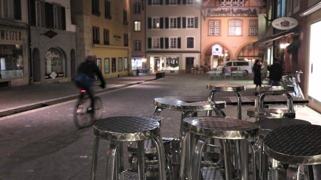 Gestapelte Barhöcker in einer Altstadtgasse.