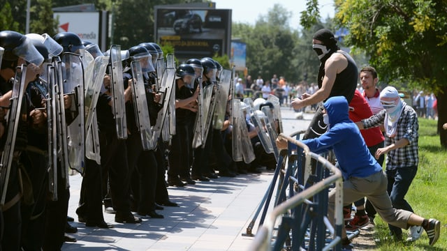 Vermummte Demonstranten stehen Sicherheitskräften in Kampfmontur gegenüber
