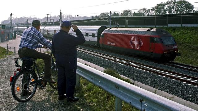 Zwei ältere Herren beobachten von einer Böschung einen vorbeifahrenden Zug.