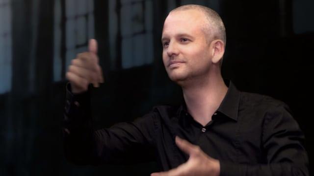 Ein dirigierneder mann mit Kurzhaarfrisur und schwarzem Hemd.