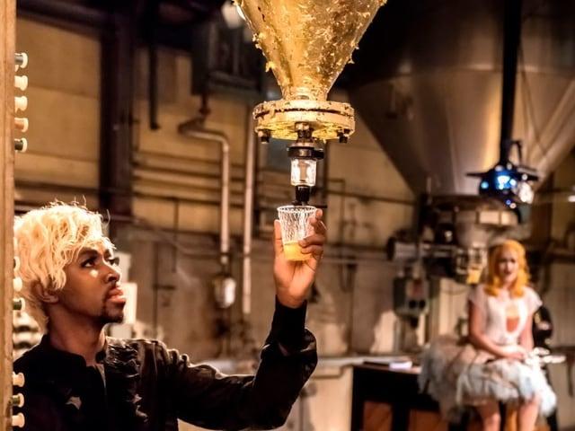 Mann schenkt Wein aus einer Turbine ein - im Hintergrund sieht man eine sitzende Frau.