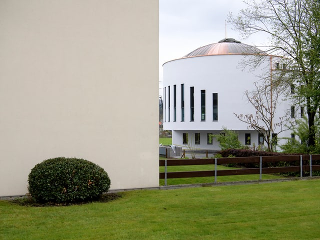 Ein weisses Gebäude mit schlitzartigen Fenstern und einer Kuppel.