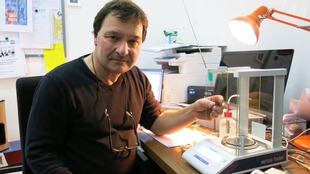 Daniel Allemann im improvisierten Labor mit einem Fläschen mit Pulver drin in der Hand