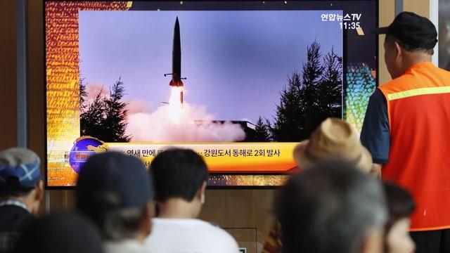 Südkoreaner schauen auf Bildschirm mit Raketentest