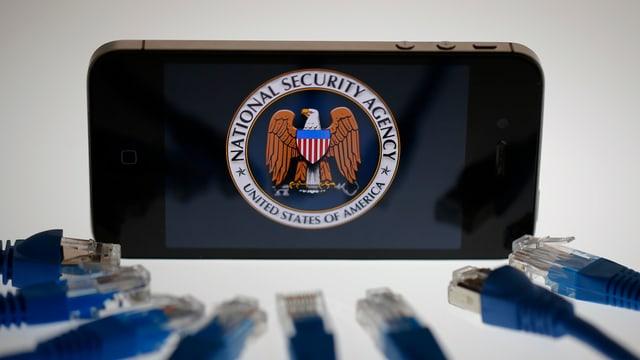 USB-Stecker vor einem Smartphone mit NSA-Symbol