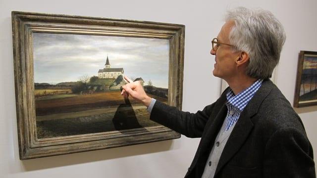 Ein Mann zeigt auf das Gemälde einer Kirche.
