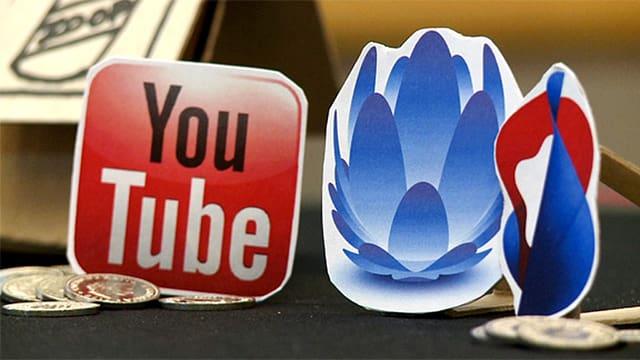 Die Logos von YouTube, UPC Cablecom und Swisscom stehen als Pappfiguren nebeneinander.