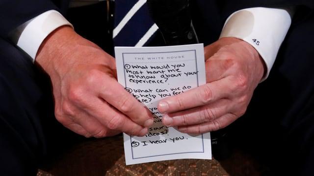 Donald Trump hält einen Notizzettel in den Händen