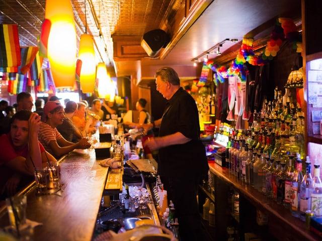 Eine Bar, man sieht den Barkeeper, ein älterer Herr mit grauen Haaren und Brille beim Ausschenken. Überall hangen Flaggen in Regenbogenfarben. Die Bar ist gut besucht.