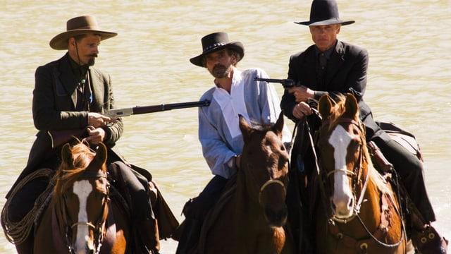 Drei Männer reiten zu Pferde. Die zwei äusserend bedrohen den Mann in der Mitte mit einem Gewehr und einer Pistole.