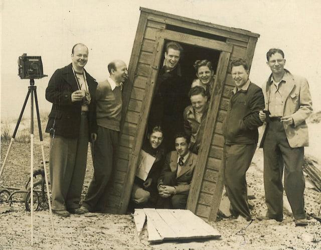 Eine Gruppe Studenten posiert in einem schrägen Holzschuppen.