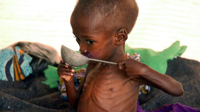 Unternernährtes Kind, das etwas Suppe löffelt