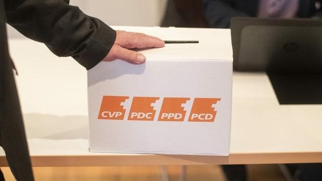 purtret d'ina urna cun si il logo da la PCD.