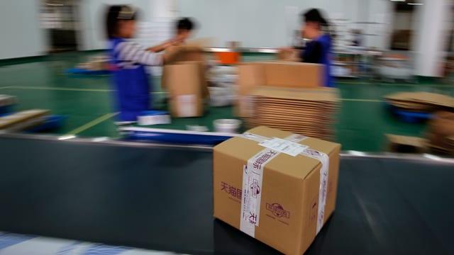 Ein Paket zeiht auf einem Band an drei Chinesischen Packerinnen vorbei.