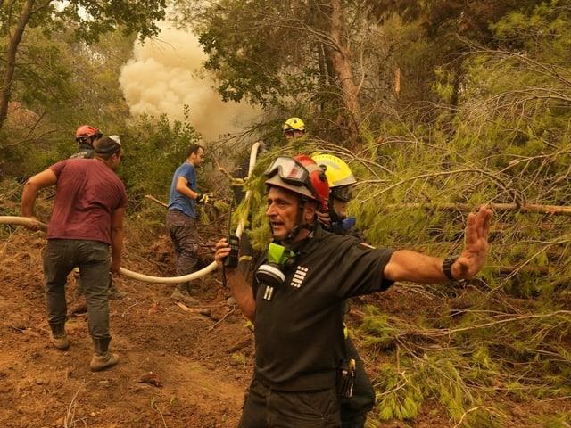 Uomini quando spengono un incendio boschivo.  Il pompiere con la radio fa segnali con la mano.