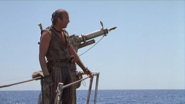 Mann am Bug eines Schiffs auf hoher See.