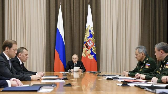 Putin an einem Sitzungstisch mit Uniformierten