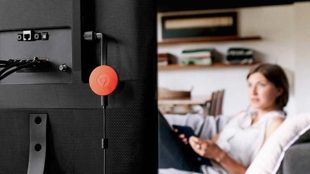 Eine rote Chromecast-Disk baumelt etwas lustlos vom HDMI-Eingang eines Fernsehers herunter.