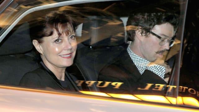 Susan Sarandon sitzt im Auto und lächelt aus dem Fenster. Daneben sitzt ein Mann mit gesenktem Blick, Brille und Schnauz.
