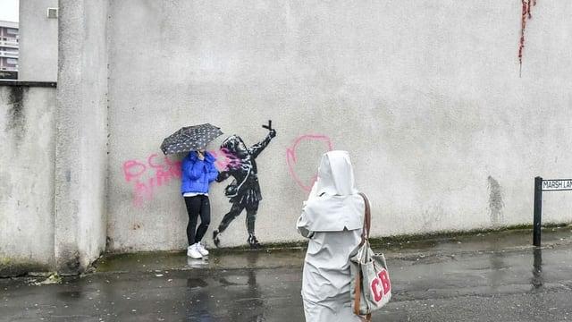 Menschen, die sich vor einem Graffiti fotografieren lassen.