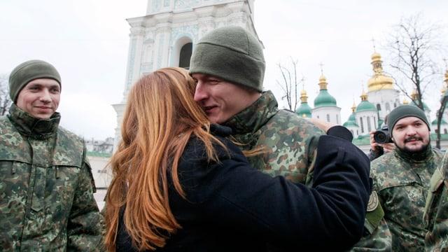 Frau umarmt jungen Mann in militärischer Tarnuniform, im Hintergrund sichtbar ist Kathedrale.