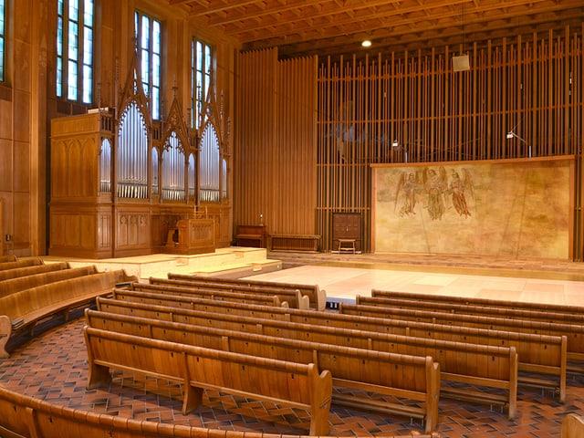 Blick in eine Kirche mit Holzbänken, auf der linken Seite die Orgel.