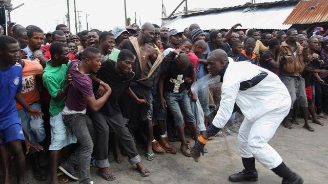 Mann in Schutzkleidung vor einer Menschengruppe