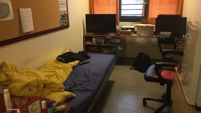 Eine Zelle mit Bett, Tisch, Bürostuhl und TV-Gerät im Seniorengefängnis.
