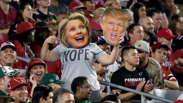 Jemand hält eine Clinton- und eine Trump-Maske in einem Stadion. Auf dem T-Shirt steht «Nope».