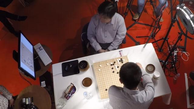 Zwei Männer an einem Tisch, links ein Bildschirm