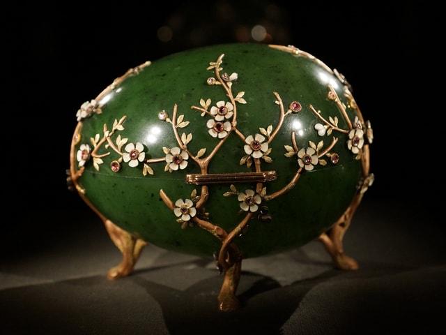 Ein grosse grünes Ei auf drei Beinen, verziert mit Goldrosen und Diamanten.