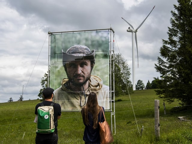 Zwei Menschen stehen im Vordergrund und schauen auf ein Kunstwerk, im Hintergrund steht ein Windrad.