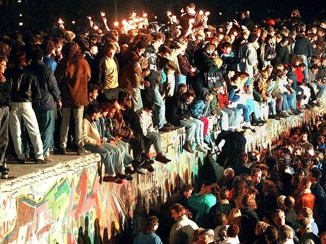 Menschen feiern ausgelassen auf der Berliner Mauer, im November 1989.