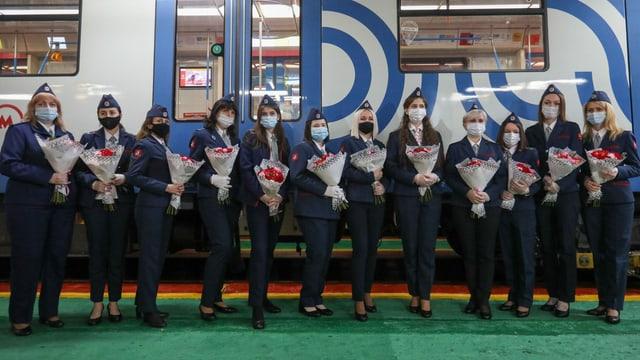 12 Frauen in Uniform stehen mit Rosensträussen in den Händen vor einem Zug.
