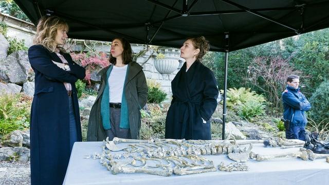 Drei Frauen mit den Überresten einer Leiche.