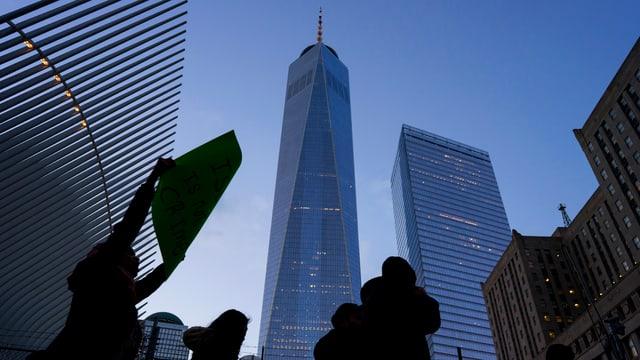 Protestierende Menschen stehen im Gegenlicht vor dem One World Trade Center.