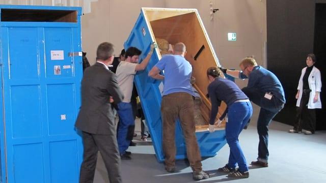 Zwei mannshohe hellblaue Kisten, die eine mit einem Soldaten drin wird von mehreren Personen hoch aufgestellt.