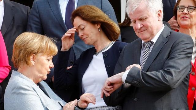 Merkel und Seehofer stehen beieinander, beide schauen auf ihre Uhren, auch andere Leute stehen drumherum.