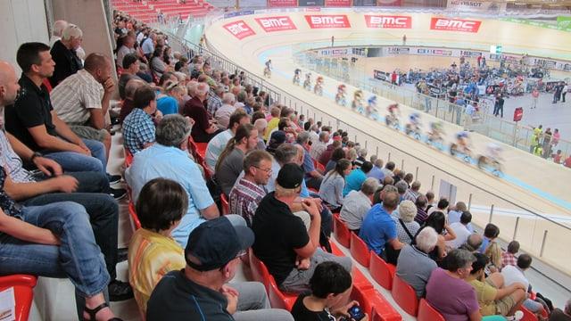 Rechts im Bild ist die Rennbahn mit Radfahrern. Link im Bild ist die gut gefüllte Zuschauertribüne.