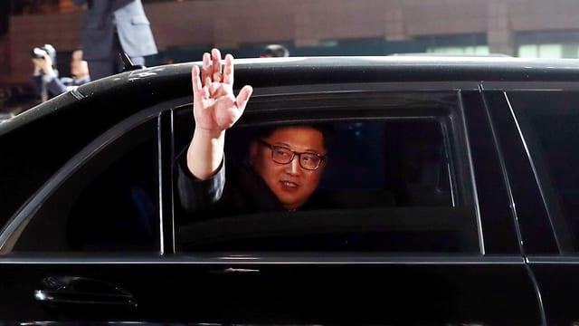 Kim Jong-un winkt aus einer Limousine.
