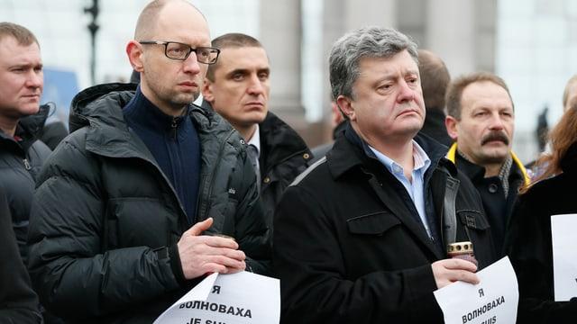Jazeniuk und Poroschenko mit Kerzen in den Händen, um sie stehen weitere Personen.