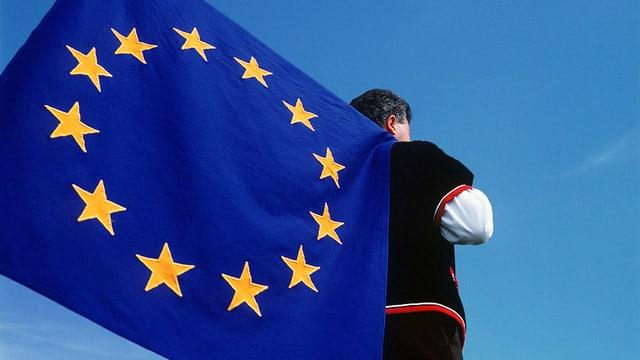 um cun vestgì tradiziunal porta ina bandiera da l'UE