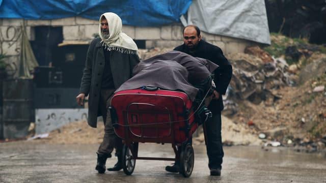 Zwei Männer stossen ihre Habseligkeiten auf einer Schubkarre durch Aleppo.