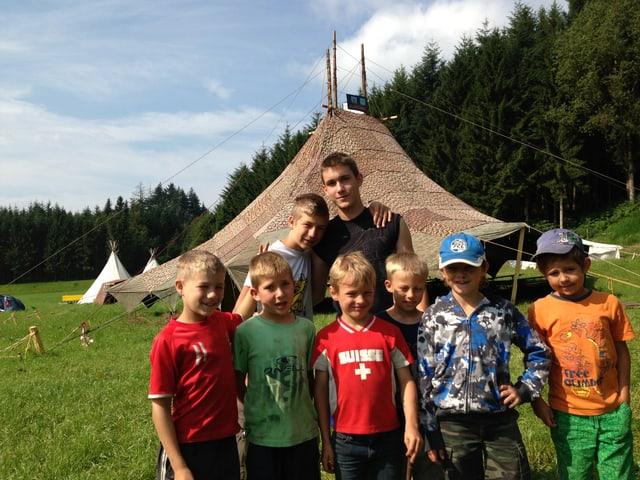 Zu sehen ist eine Gruppe Kinder in der Natur vor einem grossen Gemeinschaftszelt.